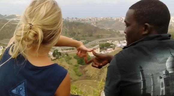 Zwei Personen blicken auf den Zaun von Ceuta.