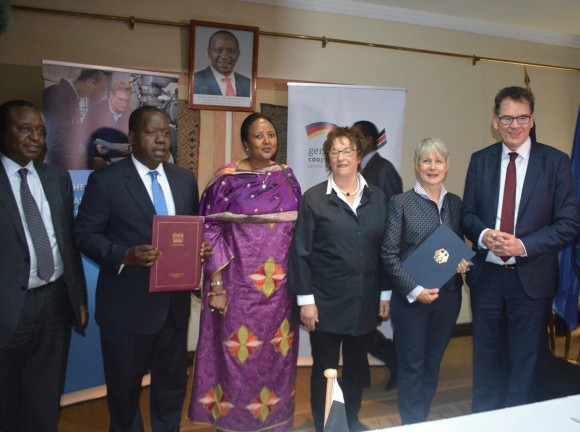 Kenya's Cabinet Secretary (CS) of Education Dr. F. Matiang'i (2nd left) and German Ambassador to Kenya Jutta Frasch (2nd right) pose with the signed MOU to establish the university. Onlooking are Kenya's Finance CS H. Rotich (far left). Kenya's Foreign Affairs CS Amina Mohammed (3rd right), Germany Federal Minister for Economic Affairs and Energy Brigitte Zypries (3rd left) and Federal Minister for Economic Cooperation and Development Gerd Müller (right) (Source: Dept. of Foreign Affairs Kenya)